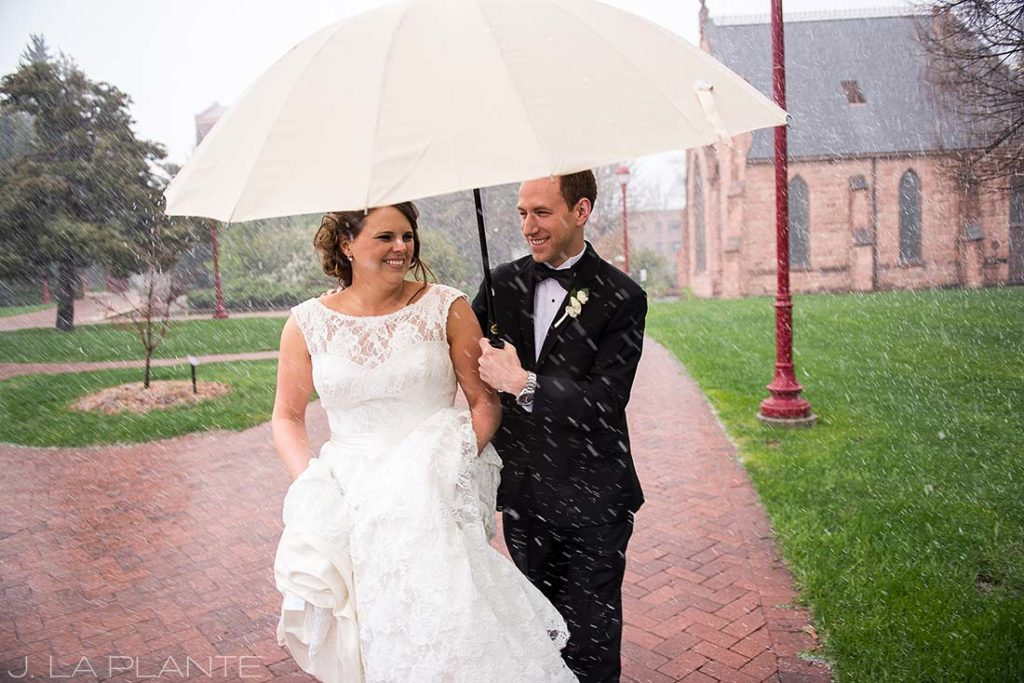 bride and groom walking in the rain with umbrella