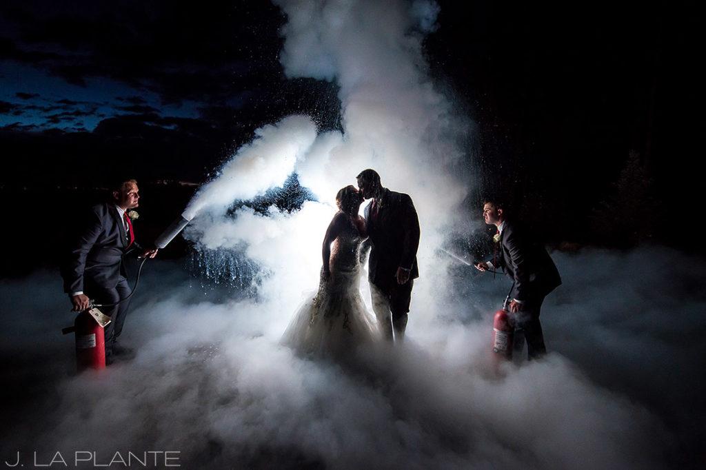 J. La Plante Photo | Winter Park Colorado Wedding Photographer | Devil's Thumb Ranch Wedding | Bride and Groom with Fire Extinguishers