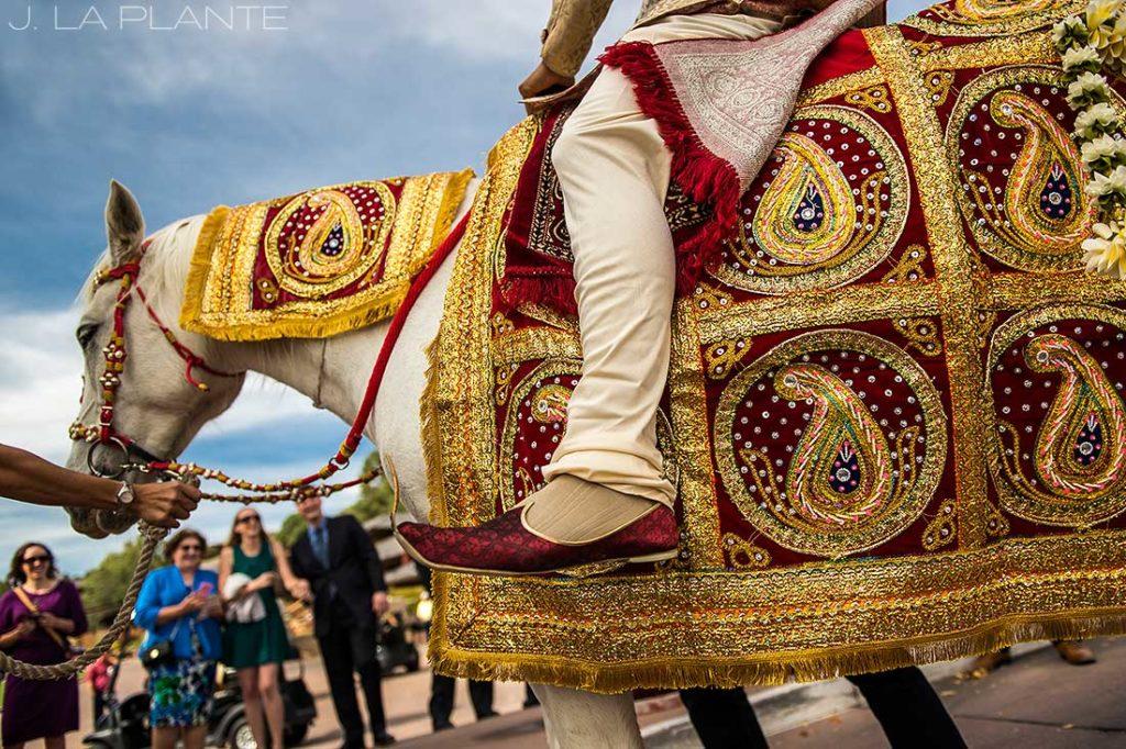 groom riding horse into wedding ceremony
