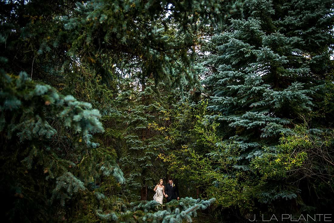 J. LaPlante Photo   Colorado Wedding Photographers   Lower Lake Ranch Wedding   Bride and Groom Walking Through Woods