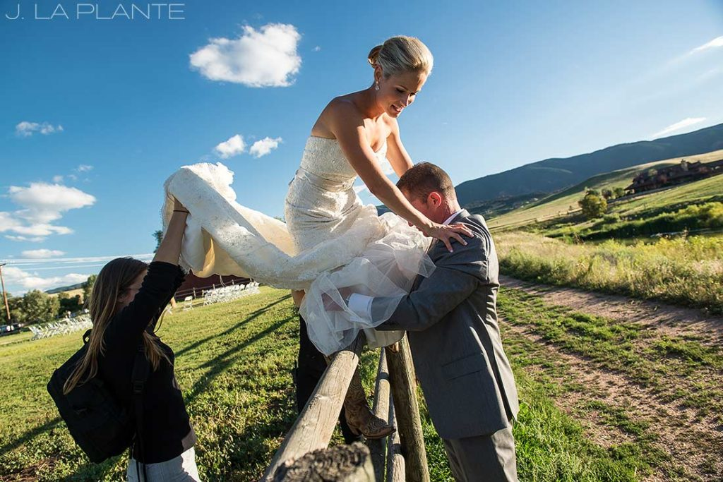 bride climbing over fence in dress