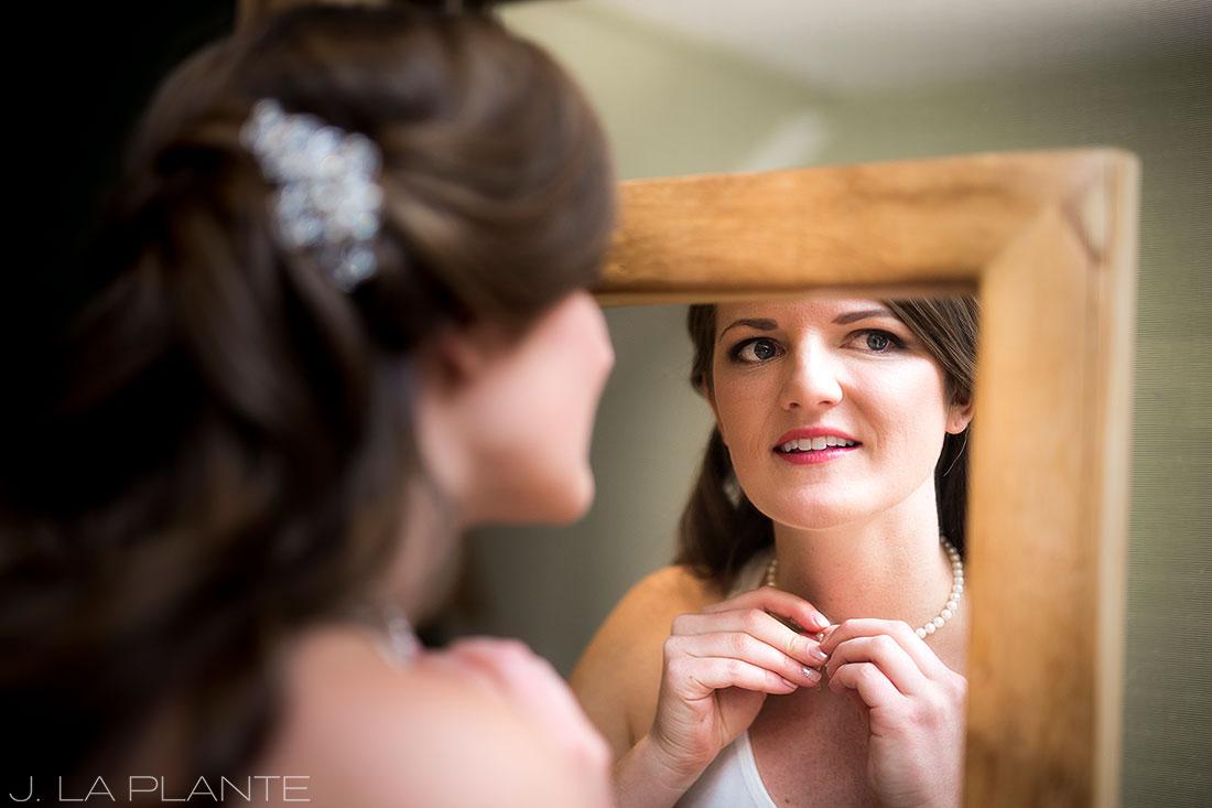 Edgewood Inn Wedding   Colorado Springs Wedding Photographer   Bride putting necklace on   J La Plante Photo