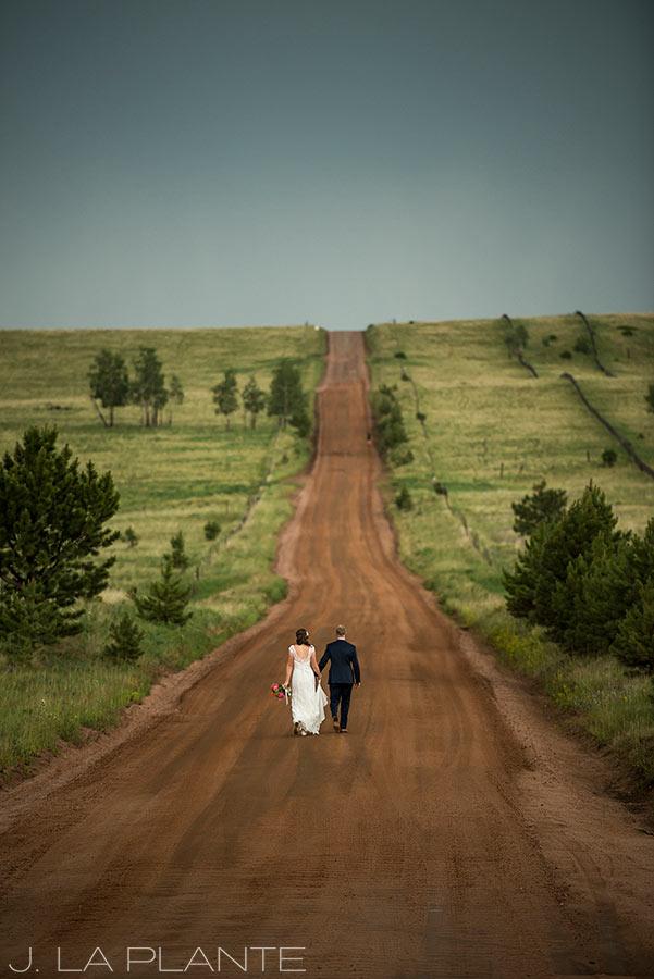 Edgewood Inn Wedding   Colorado Springs Wedding Photographer   Bride and groom walking down road   J La Plante Photo