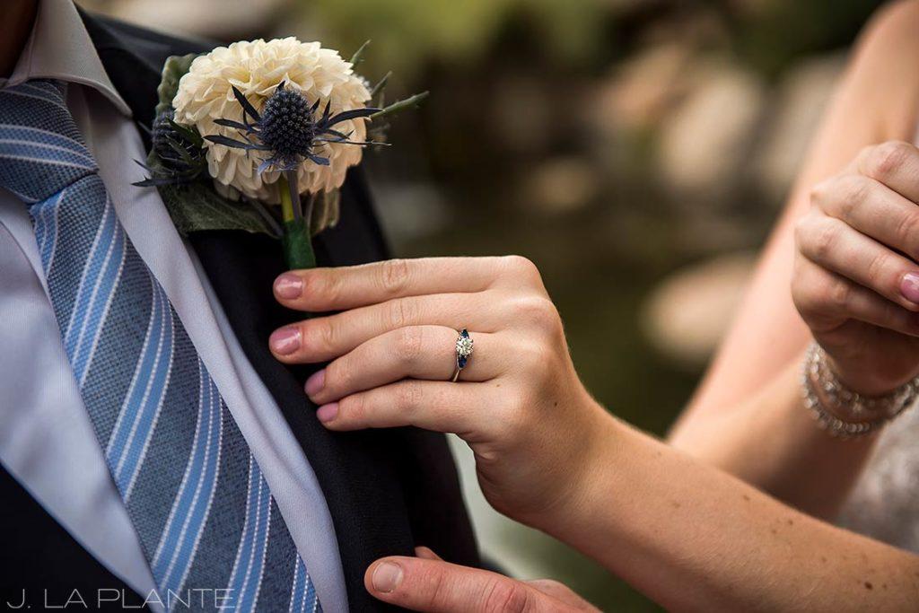 bridesmaid pinning boutonniere on groom