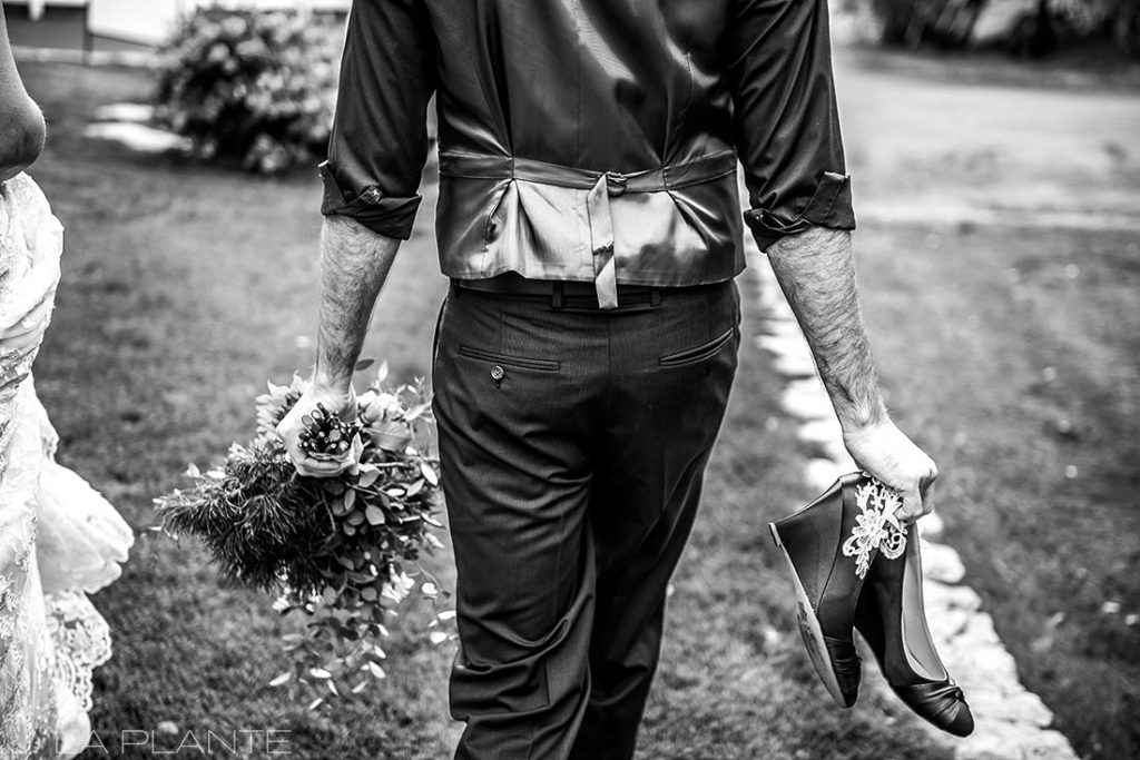 groom carrying bride's bouquet and shoes