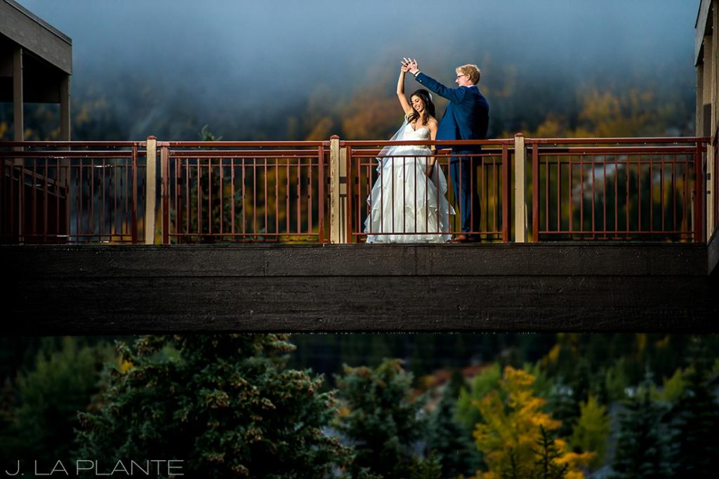 bride and groom on a bridge in the mountains
