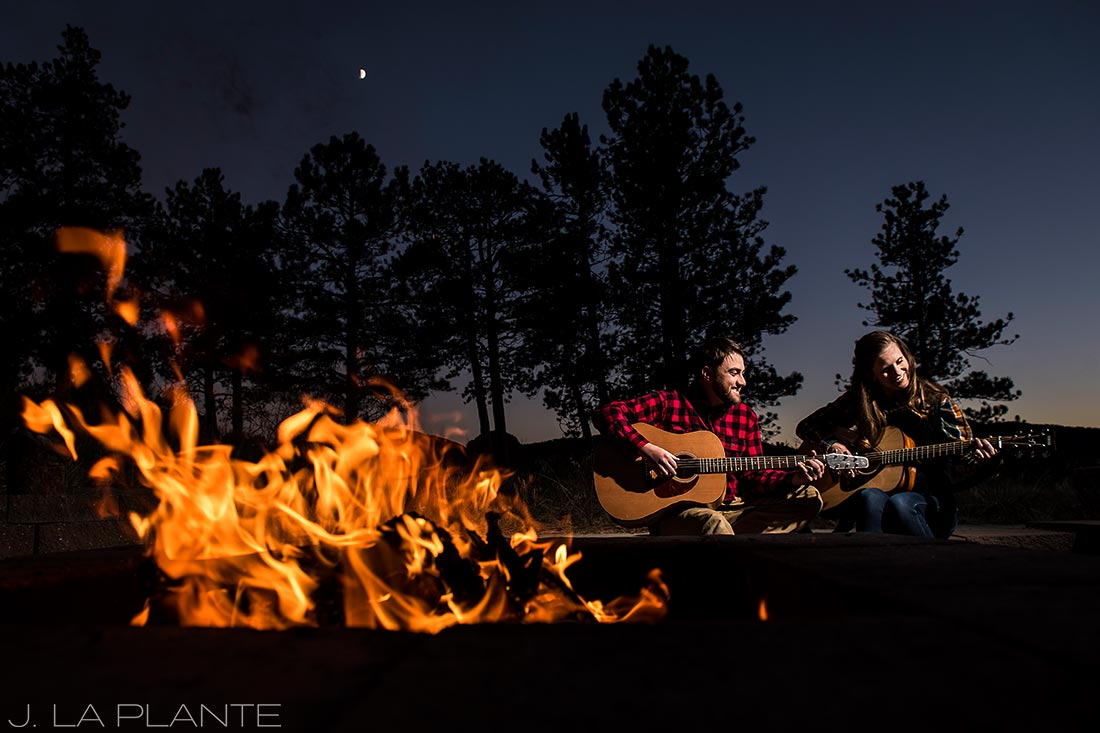 bride and groom playing guitar by campfire