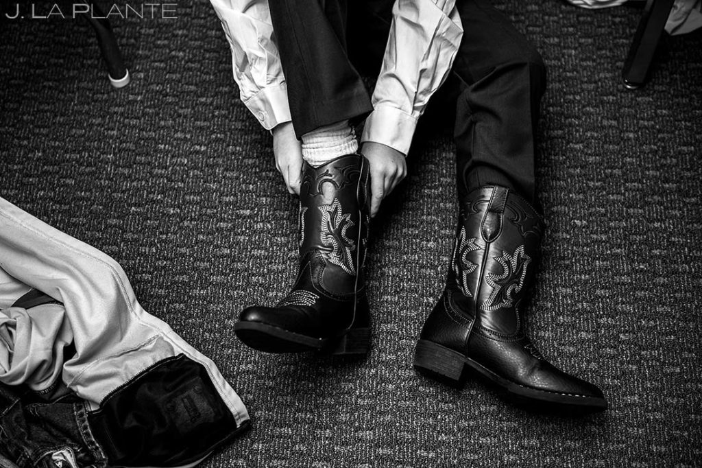 ring bearer putting on cowboy boots before wedding ceremony