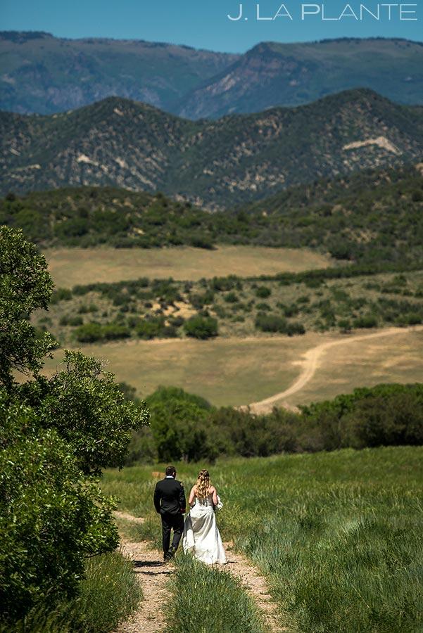 bride and groom walking around white owl ranch wedding