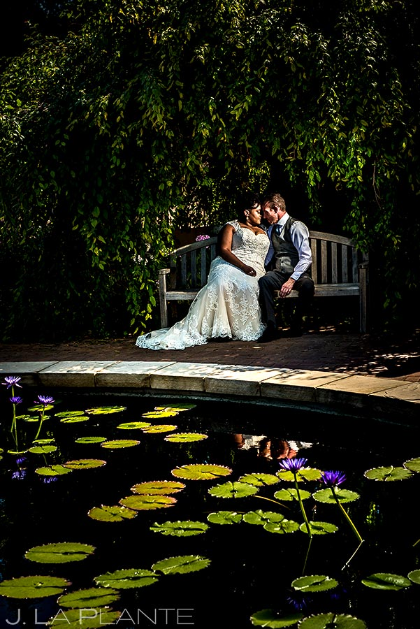 bride and groom sitting on bench next to a pond