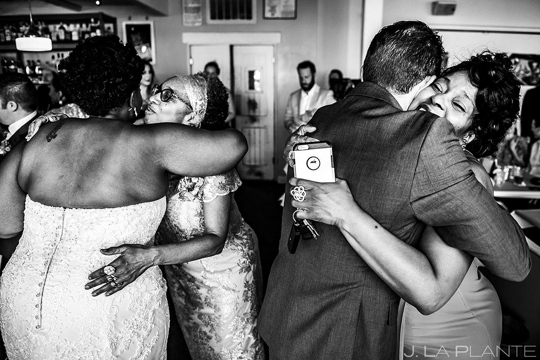bride and groom hugging their mothers