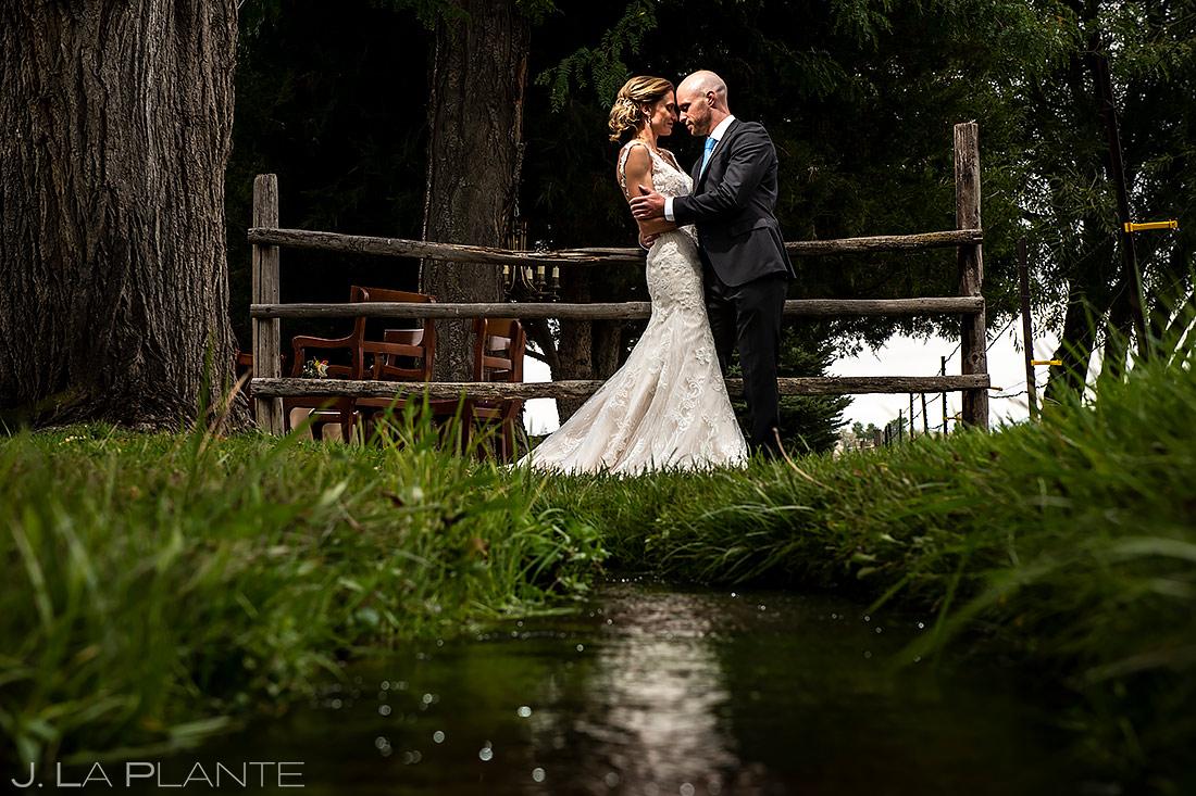 Bride and Groom by Creek   Shupe Homestead Wedding   Boulder Wedding Photographer   J. La Plante Photo