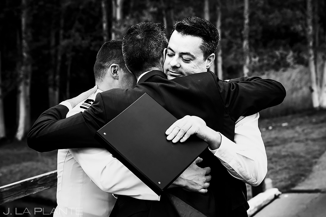 groom and groom hugging officiant after wedding ceremony