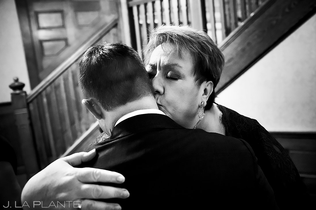 mother of the groom kissing her son on the cheek