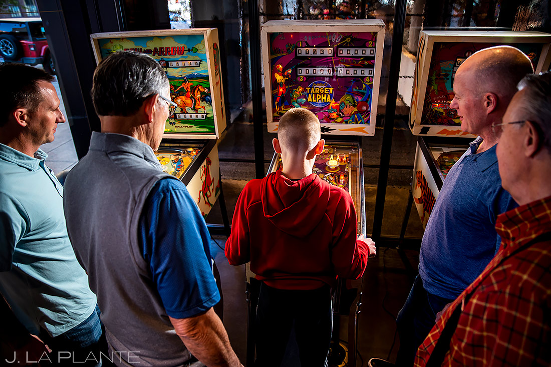 groom and groomsmen playing pinball denver photographer