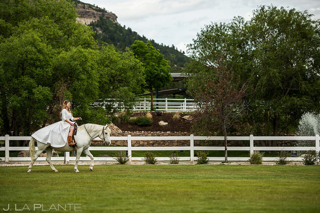 bride riding a white horse into the ceremony