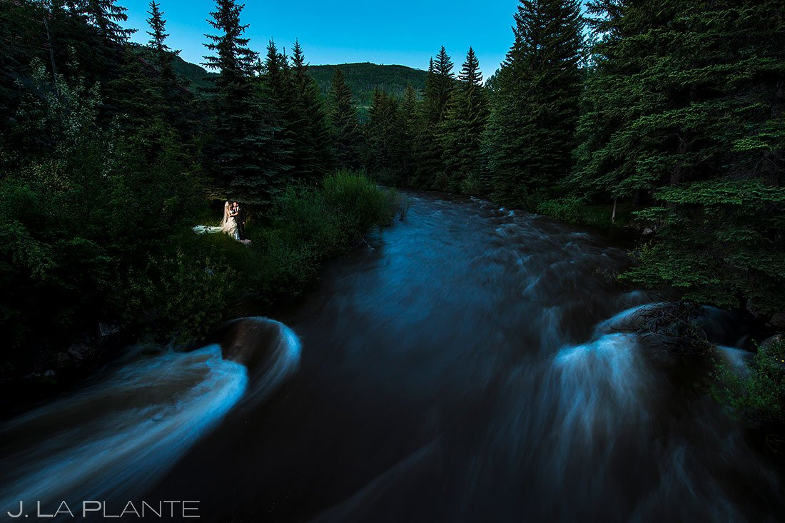 bride and groom romantic moment next to mountain river