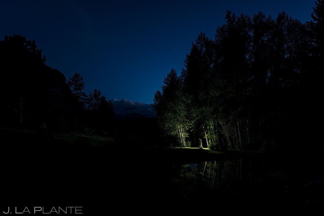 nighttime portrait of bride and groom in forest by lake