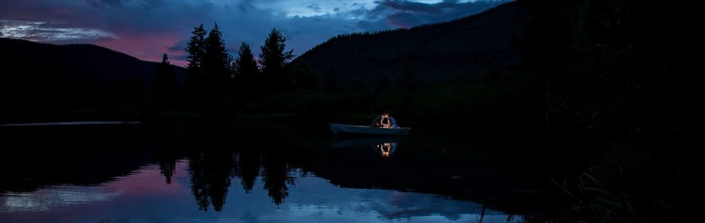 bride and groom riding in a boat at blue hour