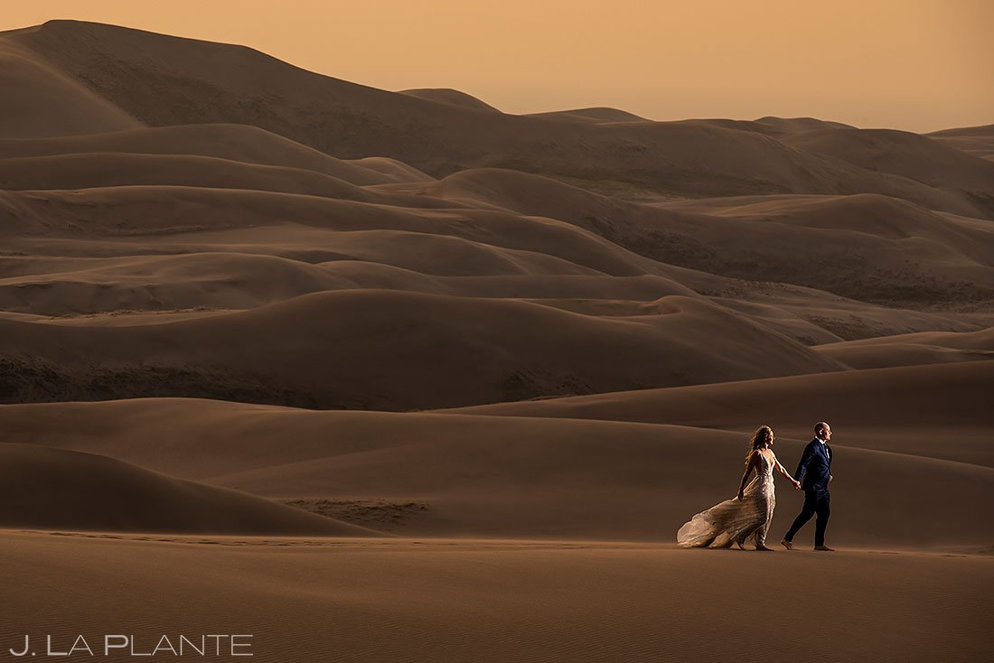 bride and groom hiking on sand dunes during post wedding photoshoot
