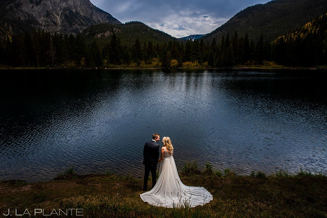 bride and groom kissing by lakeside in vail