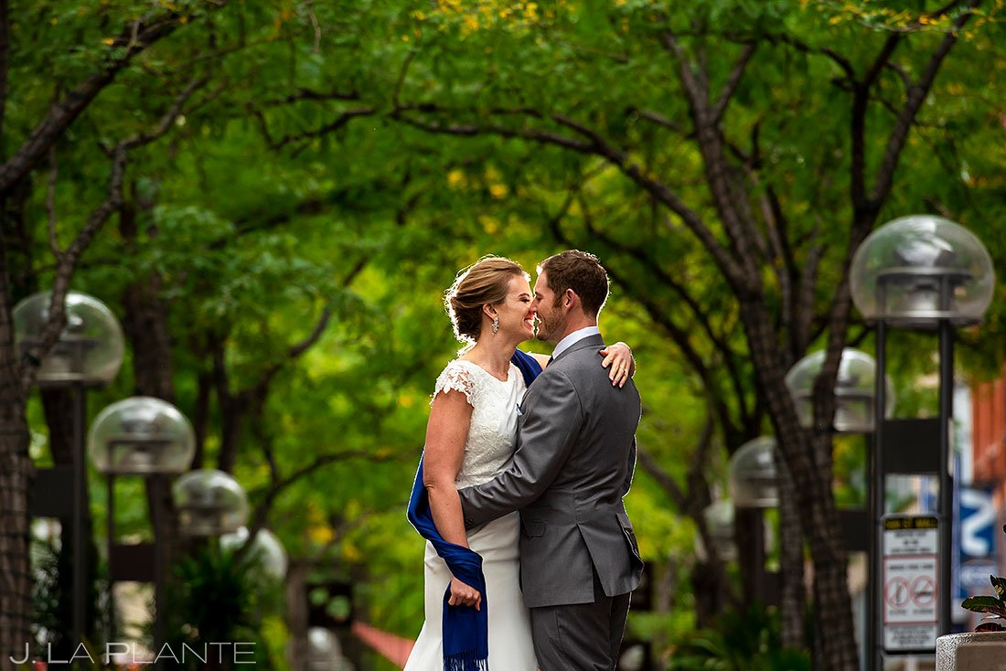 bride and groom kissing on 16th street mall in denver