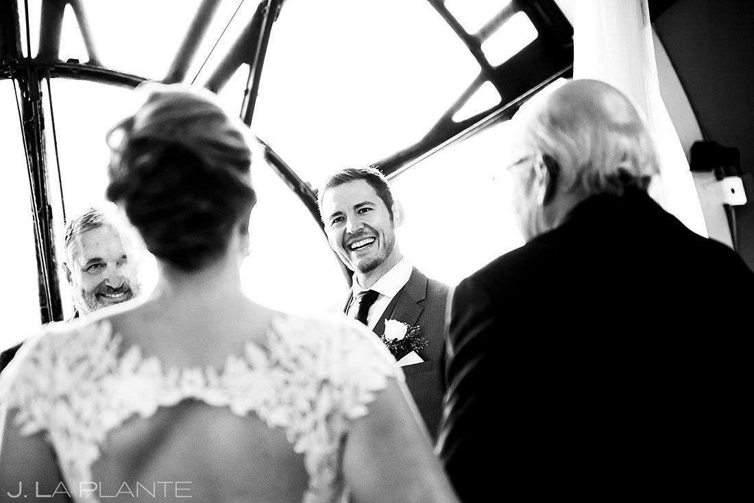 groom watching bride walking down the aisle