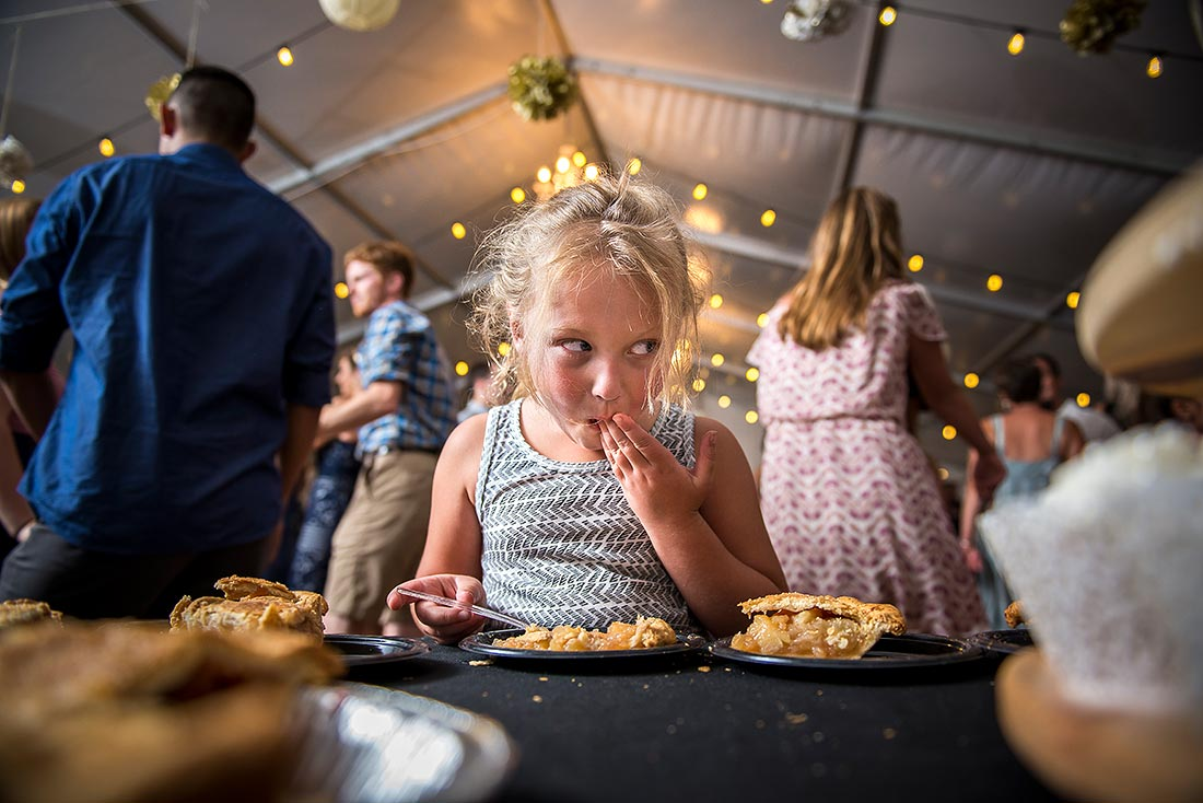 flower girl stealing cake during wedding reception
