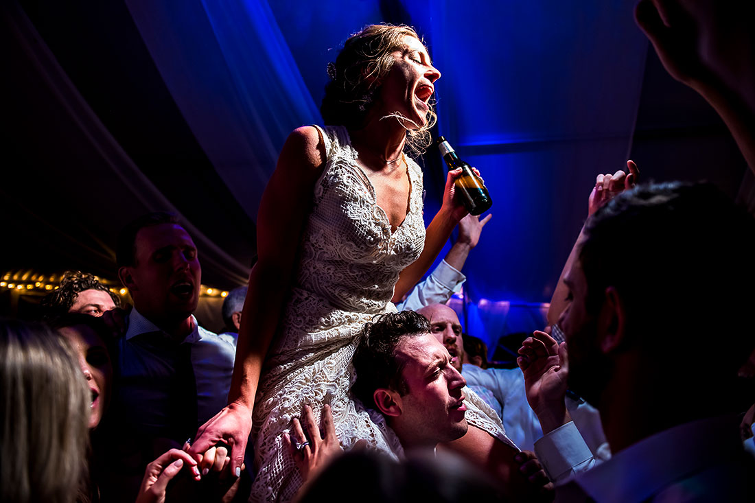 bride singing into beer bottle on the dancefloor