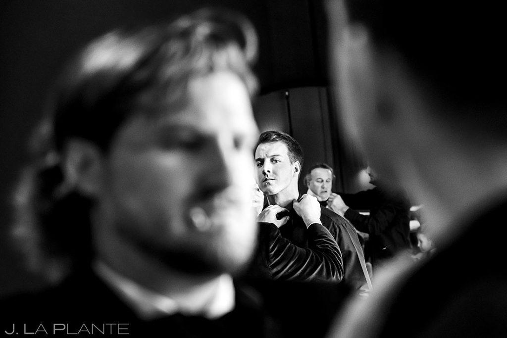 groom helping groomsman get ready