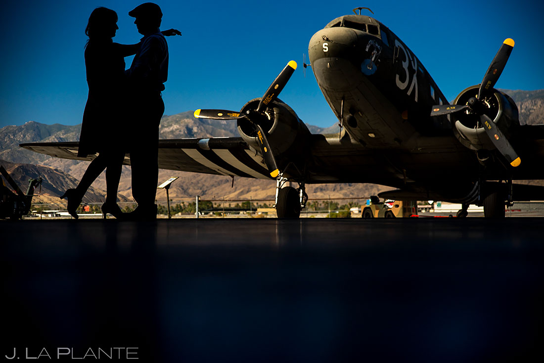 silhouette of bride and groom with antique airplane