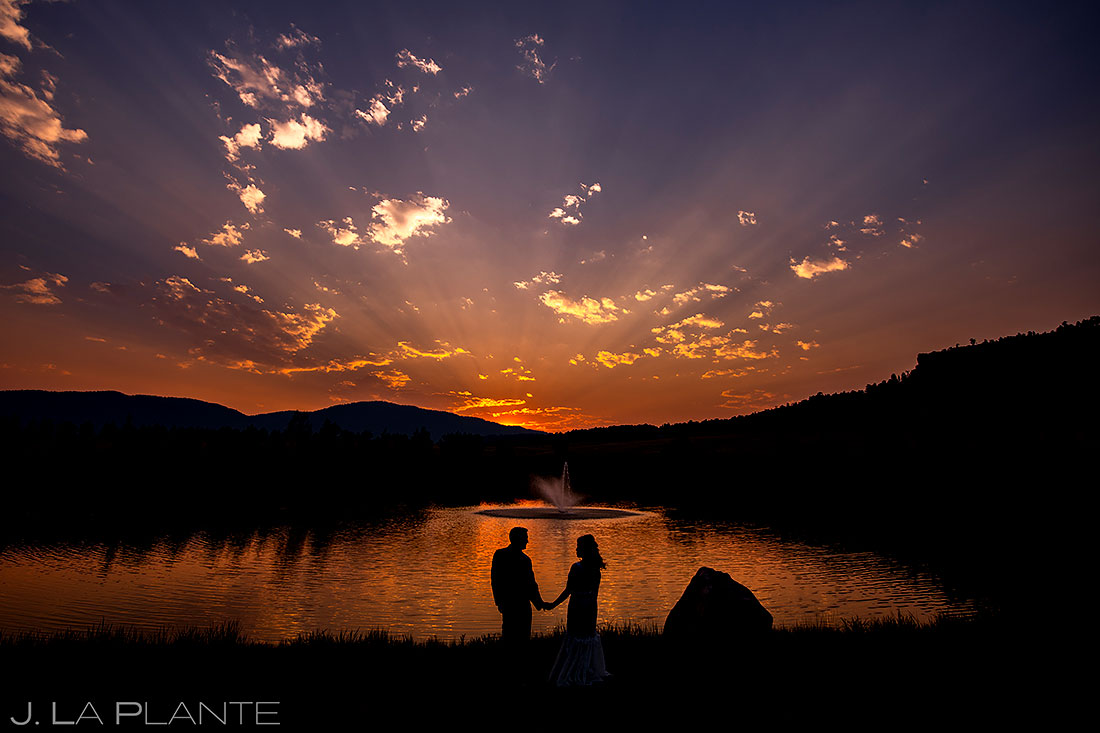 beautiful sunset wedding photo of bride and groom by a lake