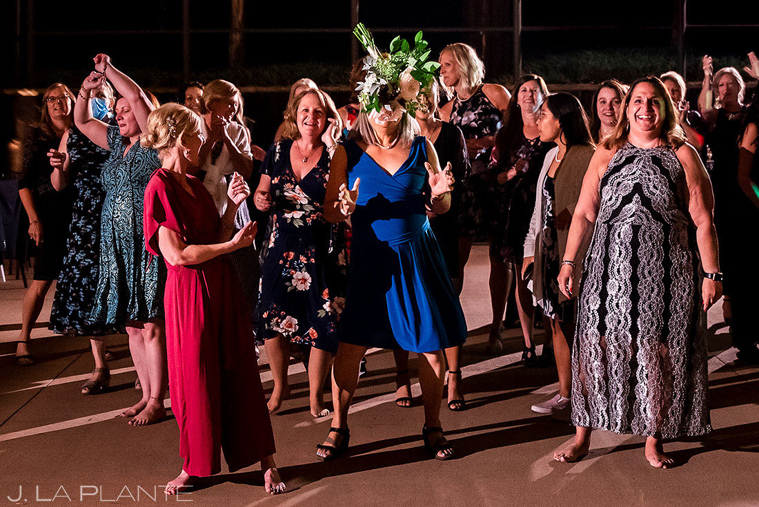 funny photo of wedding guest being hit in the face with the bride's bouquet
