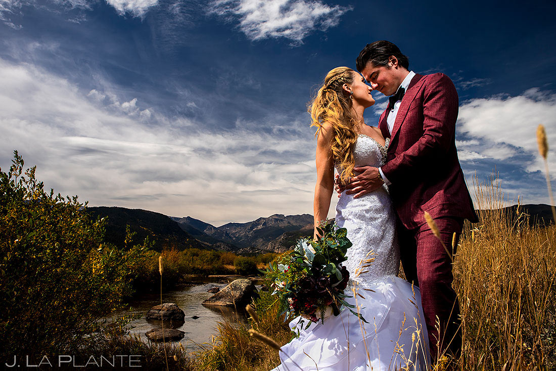 bride and groom by river in rocky mountain national park
