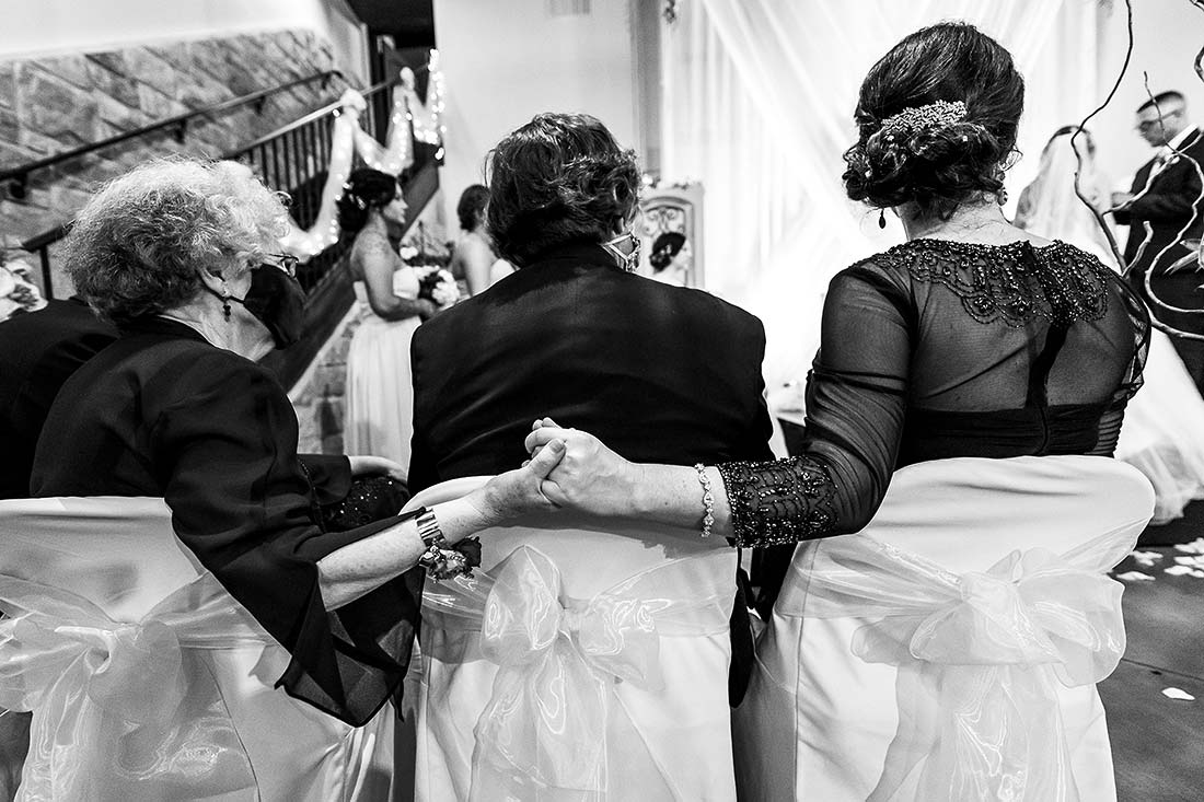 mother of the bride holding grandmother's hand during wedding ceremony