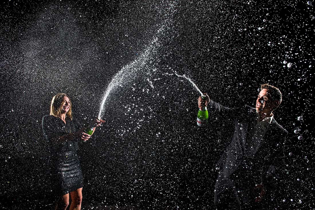 bride and groom to be spraying bottles of champagne