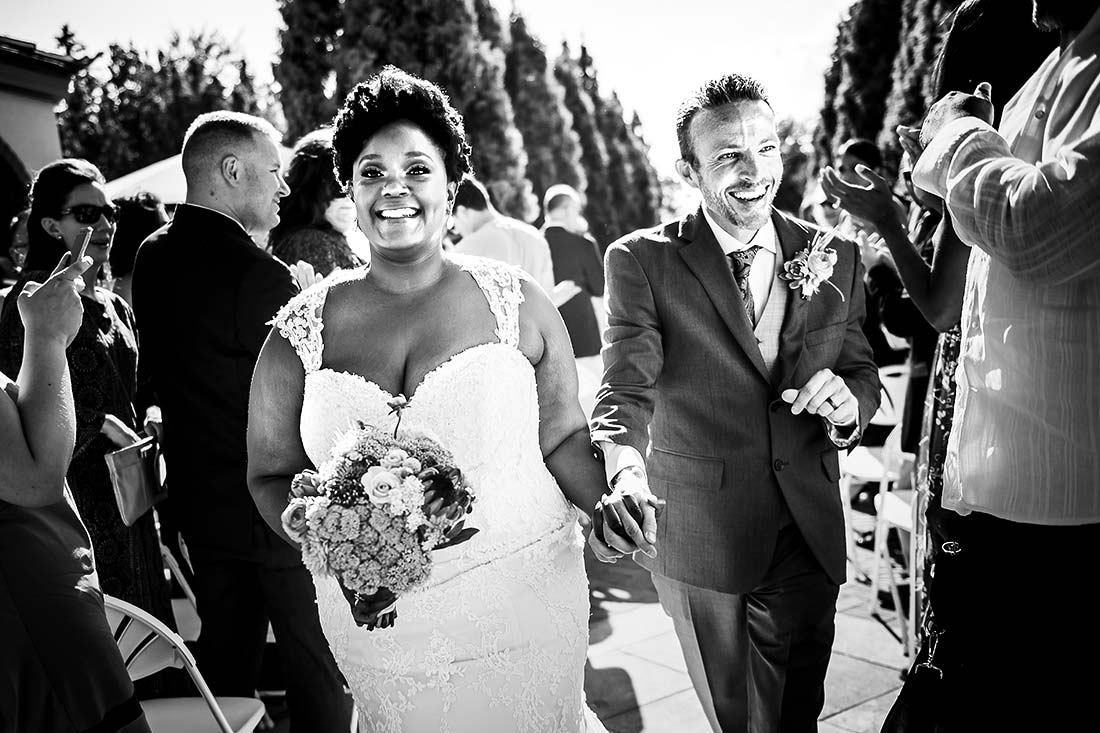 vibrant wedding photograph of bride and groom leaving ceremony