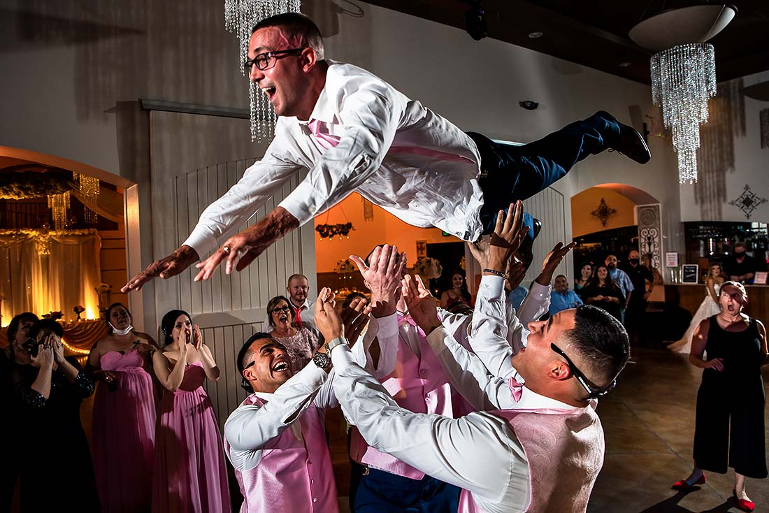 groomsmen tossing the groom into the air during dance party