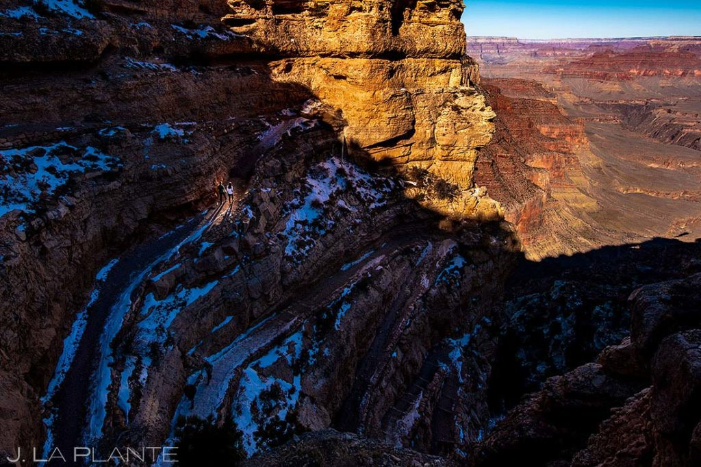 bride and groom hiking during their Grand Canyon engagement session