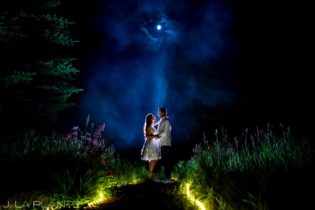 cool photo of bride and groom under a moonlit sky