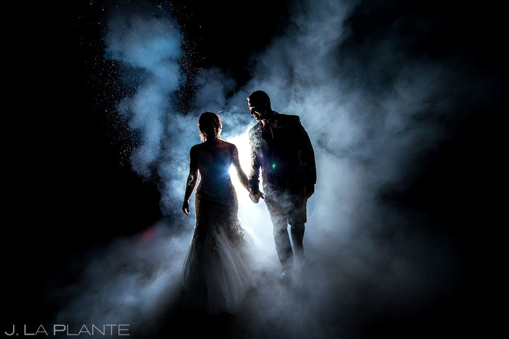 nighttime wedding photos of bride and groom with smoke at Devil's Thumb Ranch