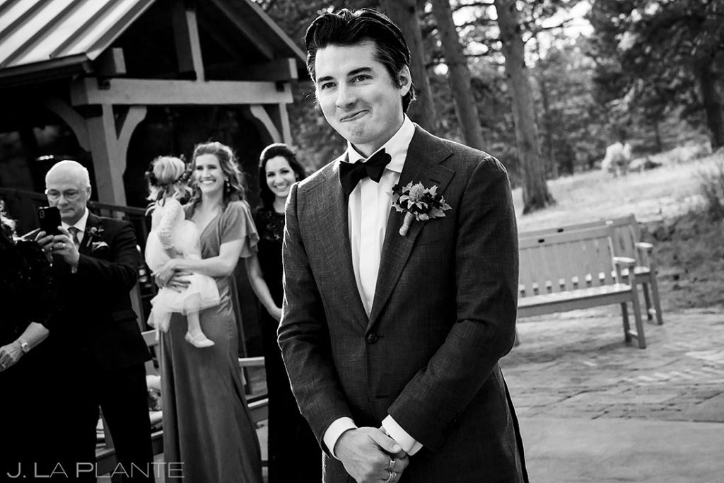 groom watching bride walk down the aisle