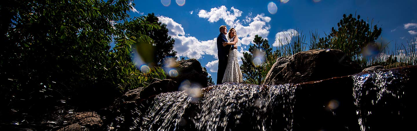 portrait of bride and groom standing on top of waterfall