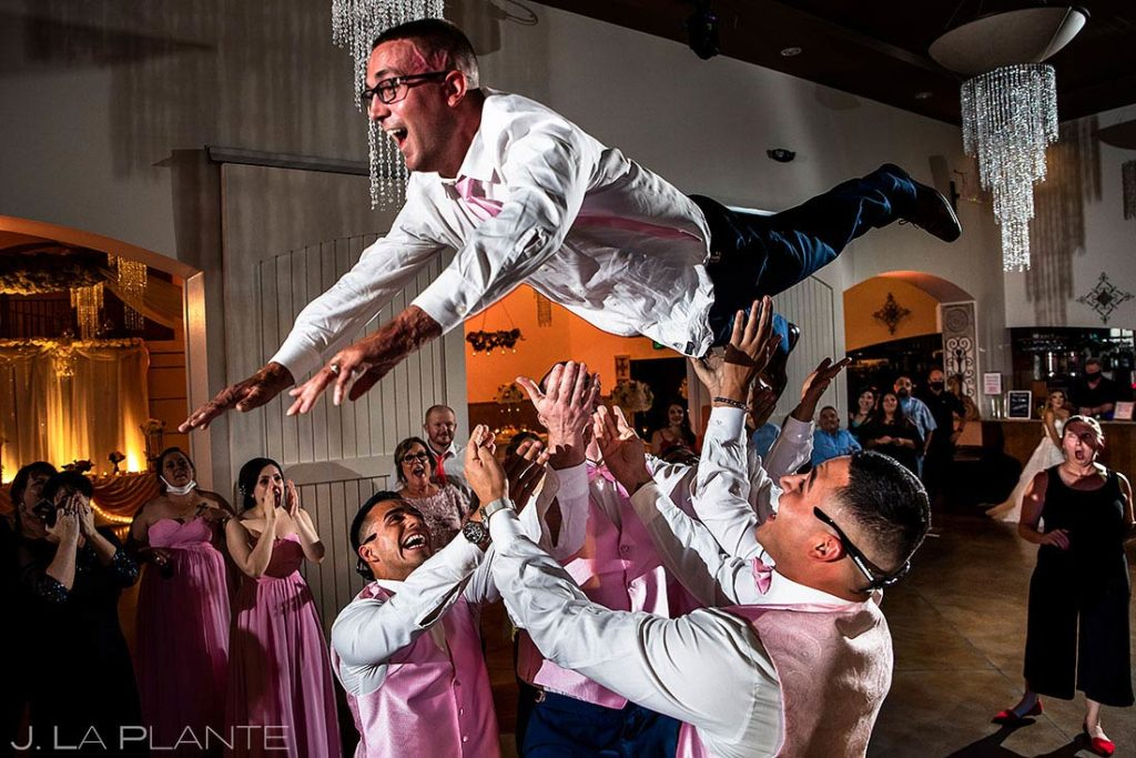 groomsmen throwing the groom into the air during reception