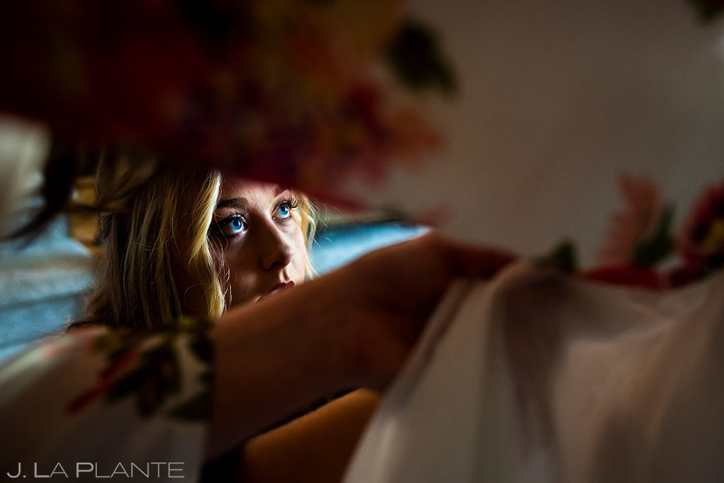 maid of honor helping the bride get into her wedding dress