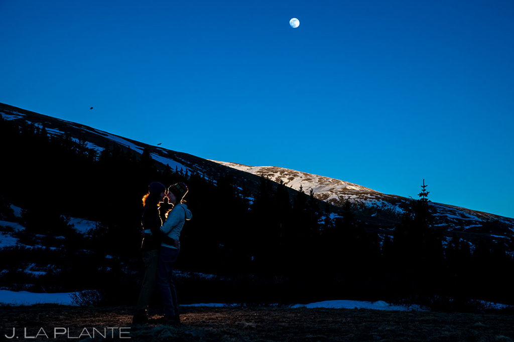 bride and groom to be kissing under the moon