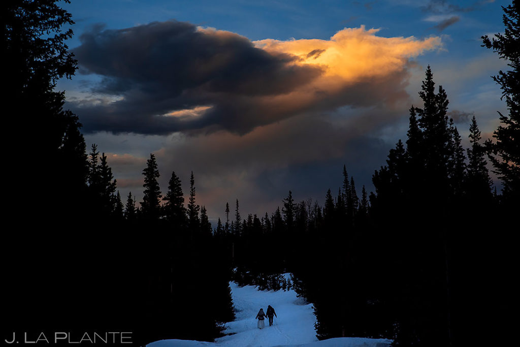 bride and groom hiking in the Rockies at sunset
