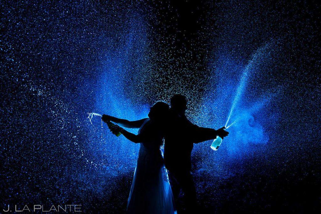 bride and groom spraying champagne at Brainard Lake elopement