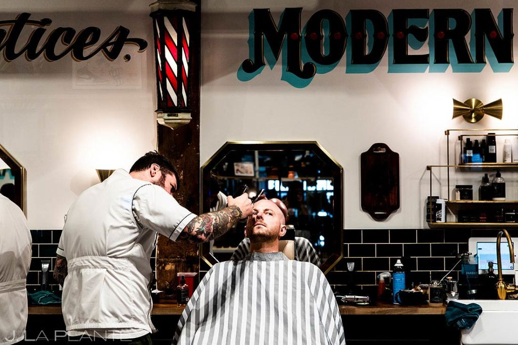 groom getting a shave at barbershop before Wellshire Event Center wedding
