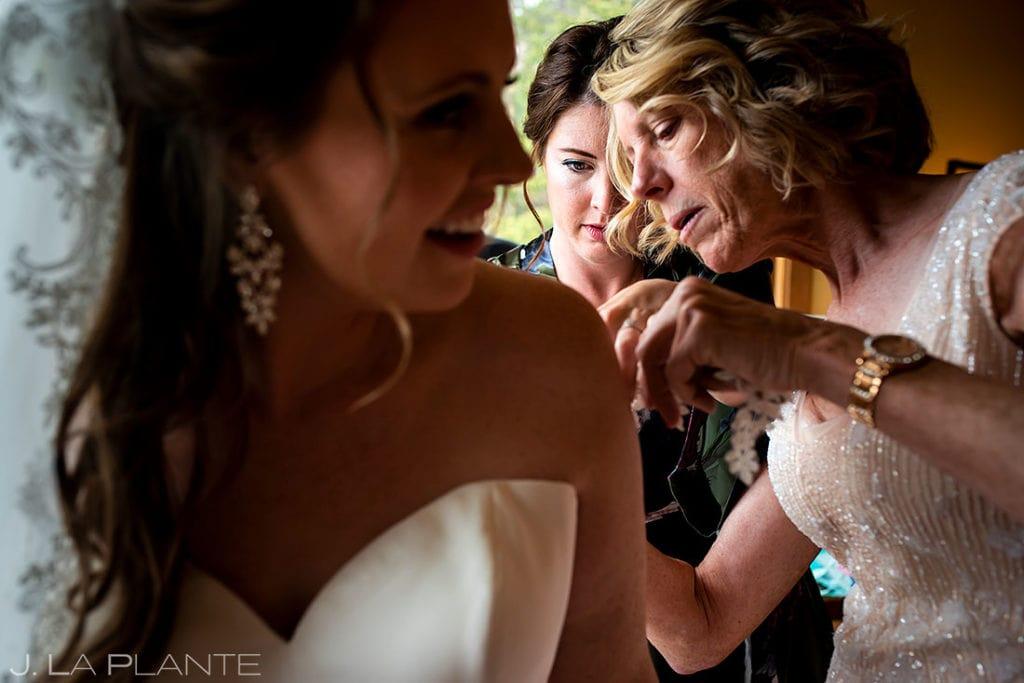 bride getting into dress before Arapahoe Basin wedding
